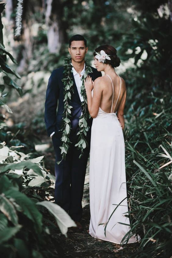 a black suit with a white shirt and a greenery garland