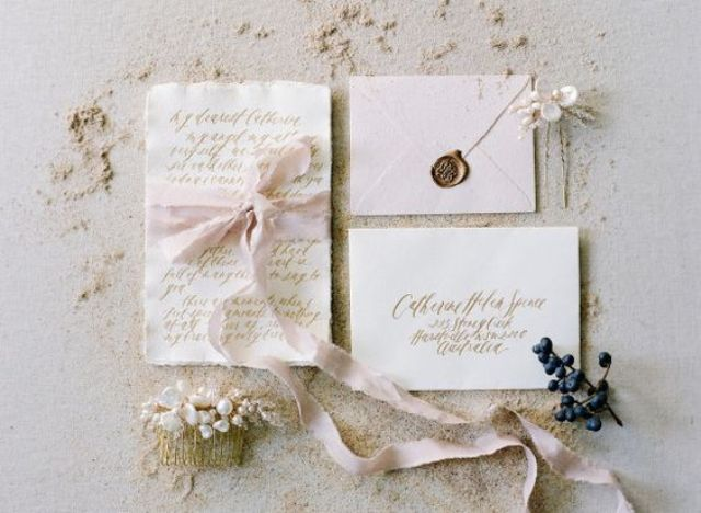 neutral wedding stationary in blush with gold calligraphy and blush ribbon