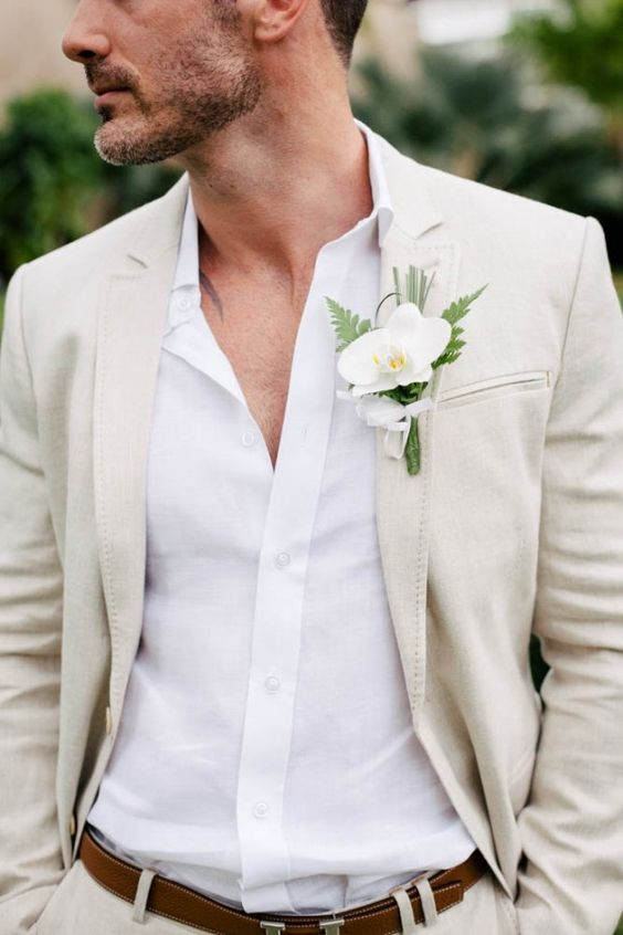 an ivory suit, a white shirt, a white orchid boutonniere