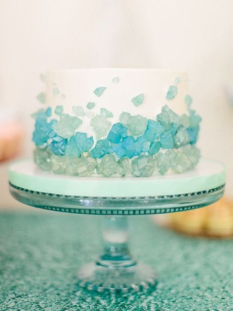 a one-tier wedding cake decorated with sea glass