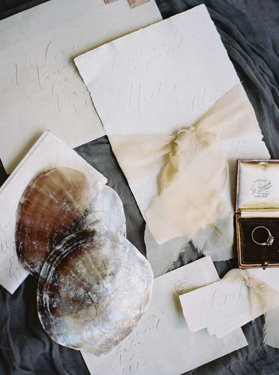 off-white wedding stationary and shells attached