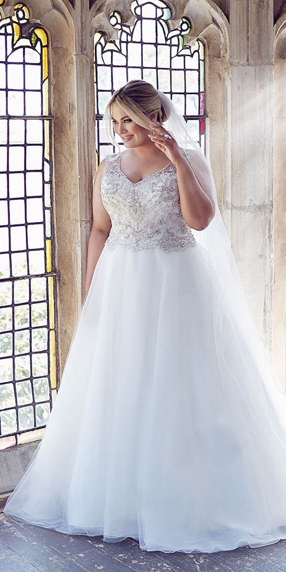 V-neck wedding dress with a heavily beaded bodice and a plain tulle skirt