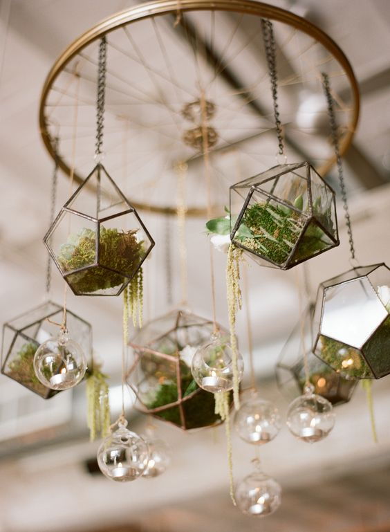 a wedding chandelier made of a large wheel and hanging terrariums filled with moss