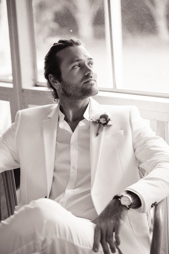 an all-white look with a suit and a shirt, a bold boutonniere