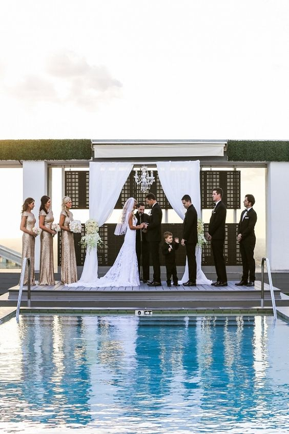glam poolside ceremony decor with a chandelier, white curtains and ivory flowers