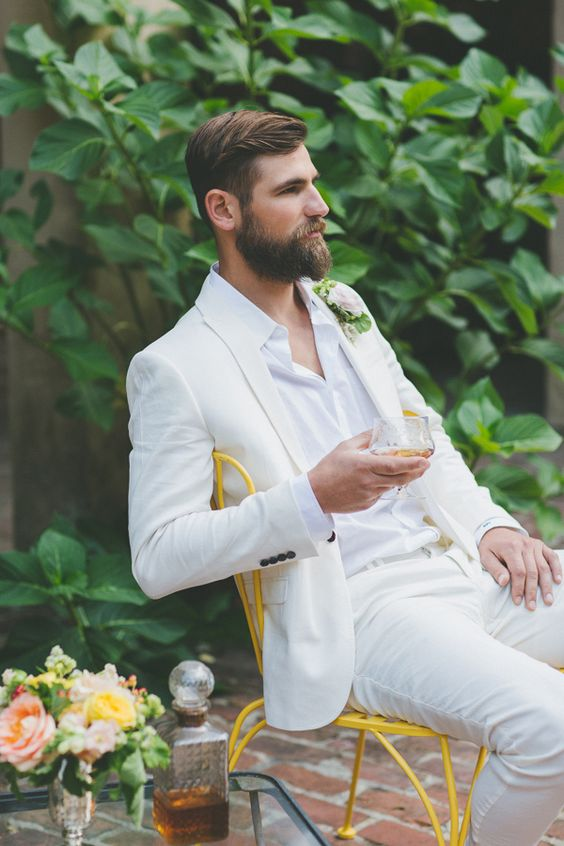 a white suit and shirt, a tropical flower boutonniere and a perfectly groomed beard