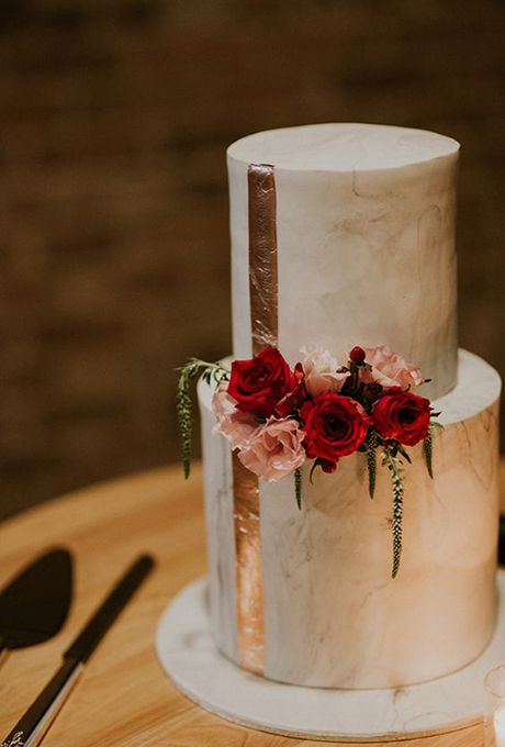 marble cake decorated with copper leaf and some fresh blooms