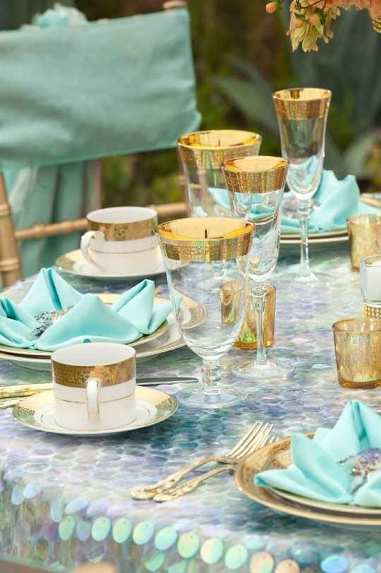 table decor with gold rim glasses and cups and a mother of pearl tablecloth