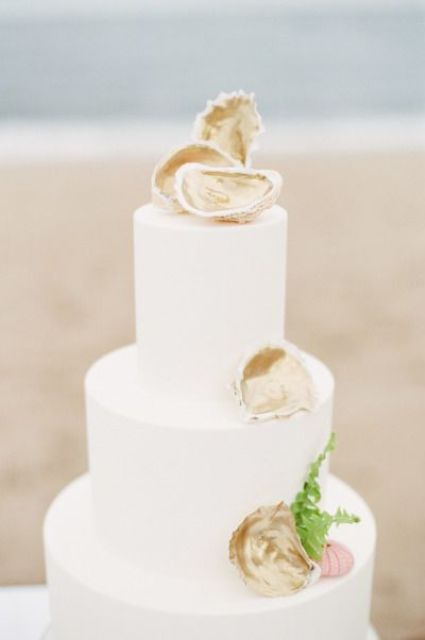 elegant white cake topped with oyster shells and greenery