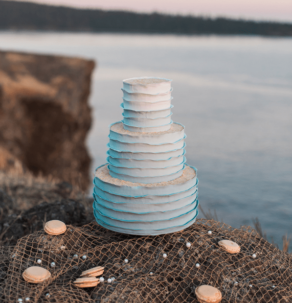 blue ruffled cake displayed on fishing net with macarons and pearls