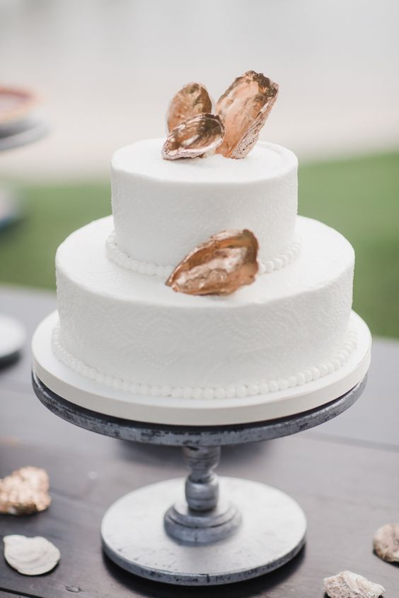 elegant white cake with gilded oyster shell decor has a distinct beach feel