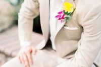 31 neutral suit with a white shirt and a bold floral boutonniere