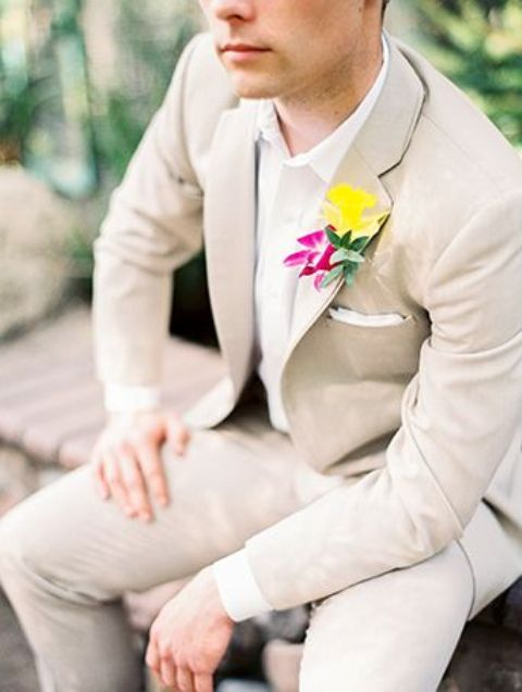 neutral suit with a white shirt and a bold floral boutonniere