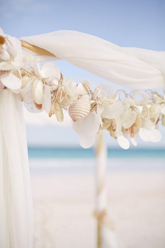 a garland of seashells accents the wedding chuppah