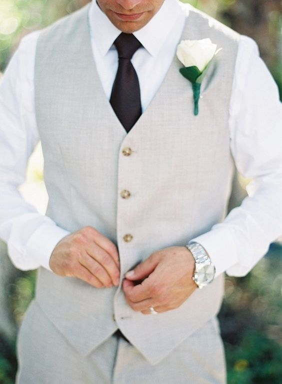 a grey vest and pants, a white shirt and a black tie