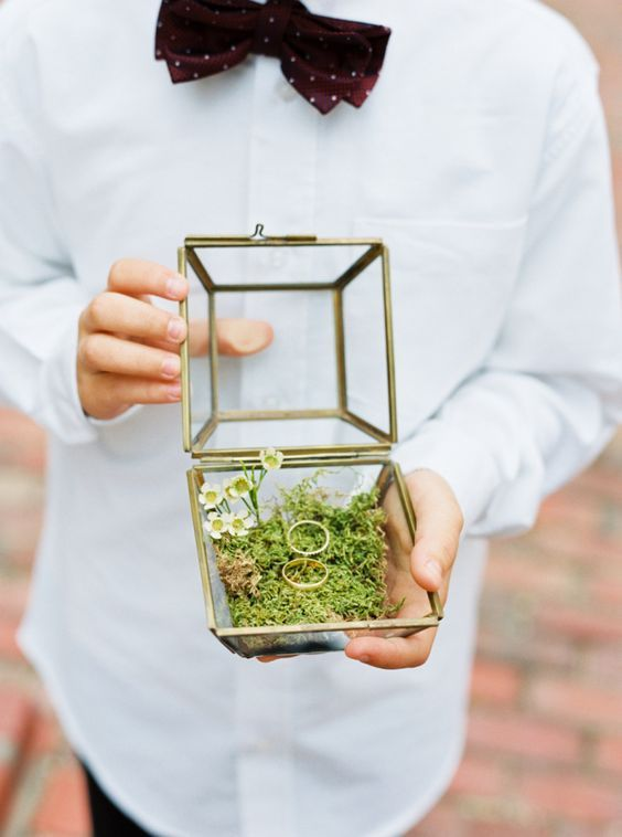 terrarium filled with moss and some flowers for a ring box