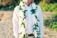 34 beige pants, a white shirt and a floral garland to highlight that it's a tropical wedding