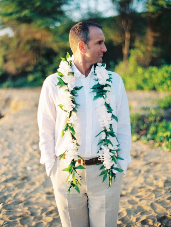 beige pants, a white shirt and a floral garland to highlight that it's a tropical wedding
