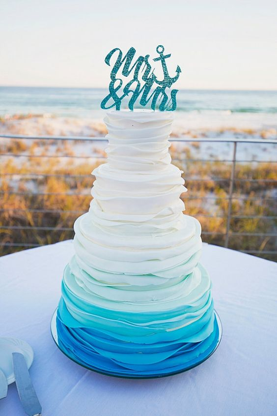 ruffle ombre wedding cake in shades of blue and a sparkling cake topper