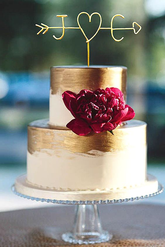 white cake decorated with gold leaf with a bold bloom