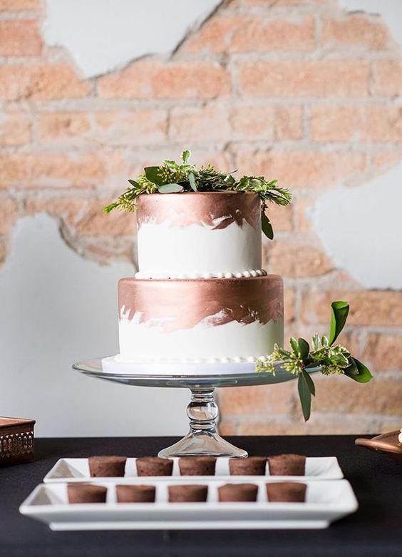 white wedding cake with copepr leaf decor and fresh greenery
