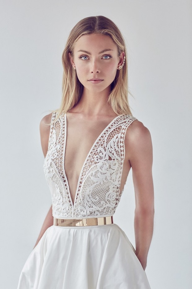wedding gown with a plunging neckline and thick straps made of lace, a plain skirt with pockets