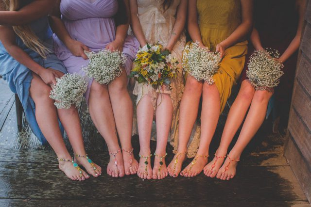 The bride and her bridesmaids were wearing foot jewelry and carried baby's breath bouquets