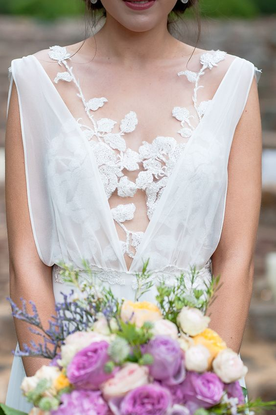 a flowy wedding dress with a lace flower top and thick straps over it