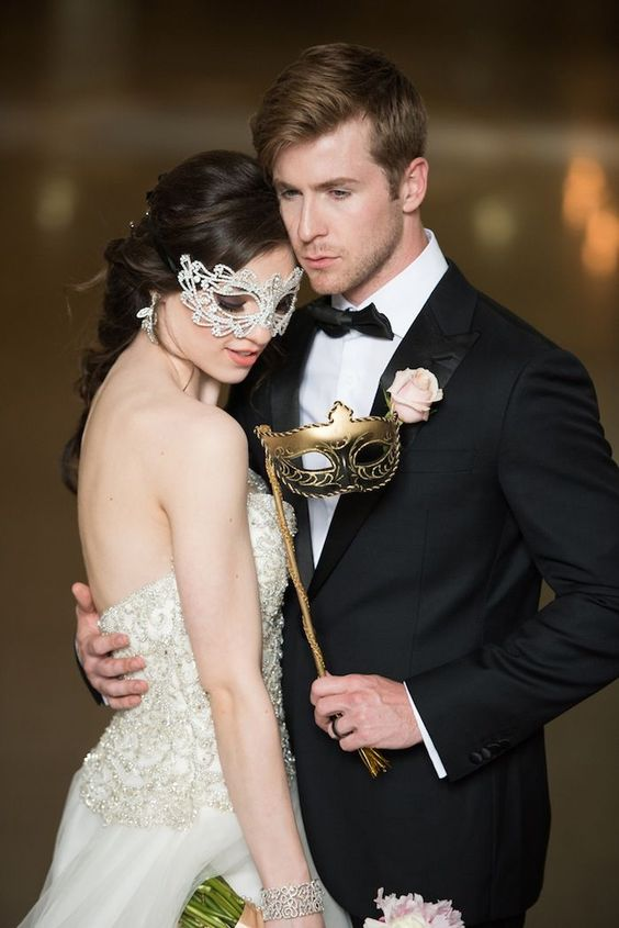 a glam masquerade couple in white and gold masks