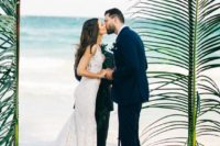 02 an elegant tropical wedding arch topped with only palm branches