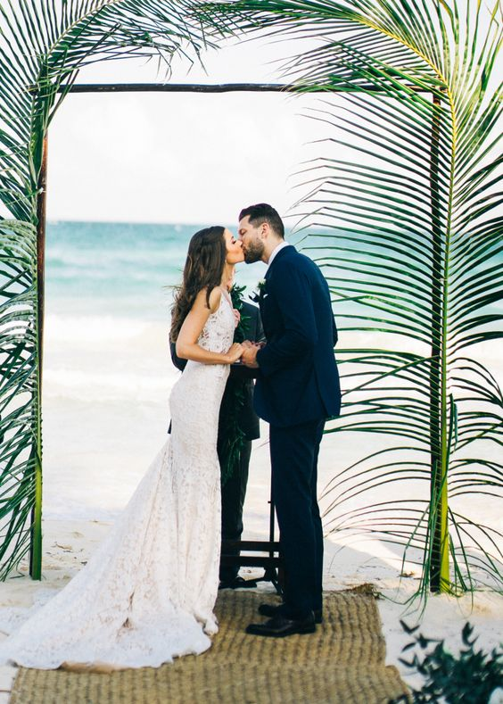 an elegant tropical wedding arch topped with only palm branches