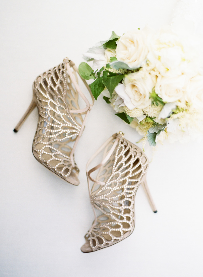 Glam bejeweled wedding heels of the bride and her neutral bouquet