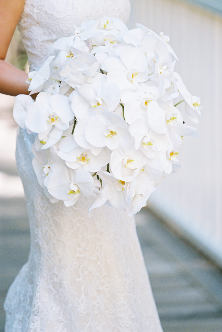 The bride chose an oversized white orchid bouquet as these are the favorite flowers of her mom