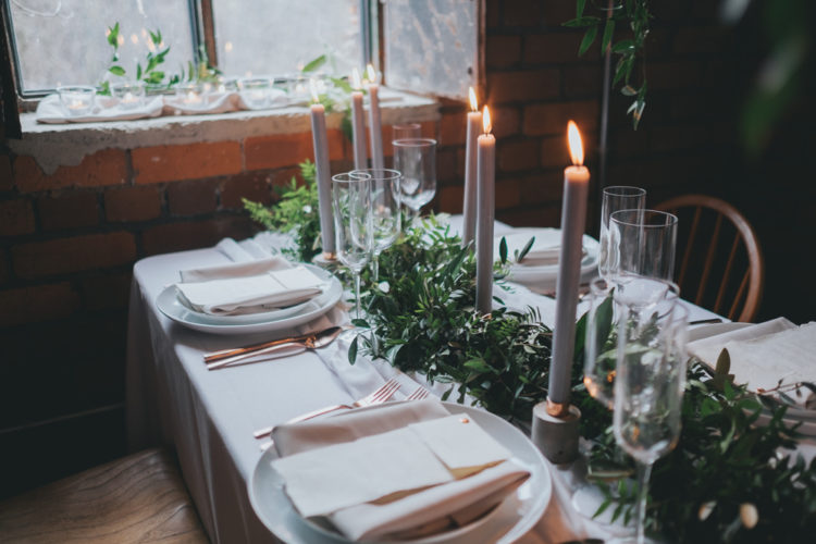 The wedding tablescape was decorated with a greenery table runner, candles and marble candle holders and copper cutlery for a texture
