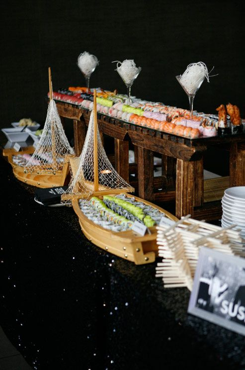 a creative sushi bar with food in ships and on wooden stands