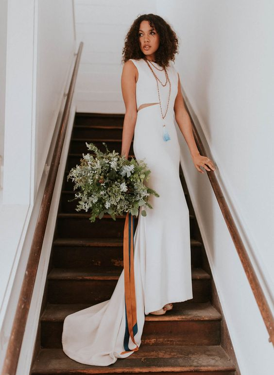 sleeveless wedding dress with small side cutouts and a train