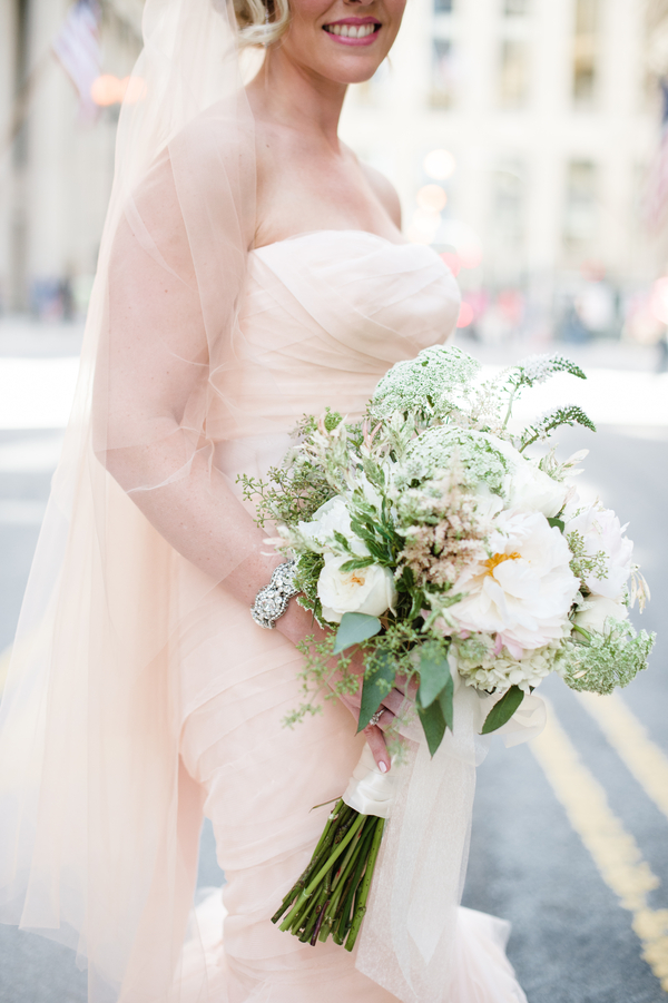 She carried a neutral textural bouquet with greenery