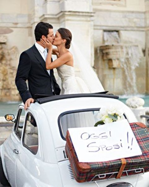 a couple in a retro Fiat taking a photo next to Fontana di Trevi