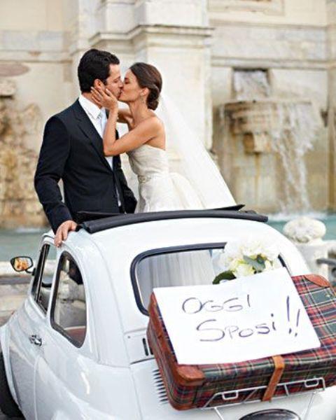 a couple in a retro Fiat taking a photo next to Fontana di Trevi