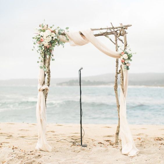 driftwood wedding arch with ethereal fabrics and neutral florals