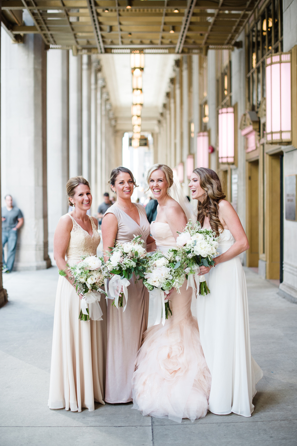 The bridesmaids were wearing mismatching neutral gowns and the maid of honor was wearing a white one