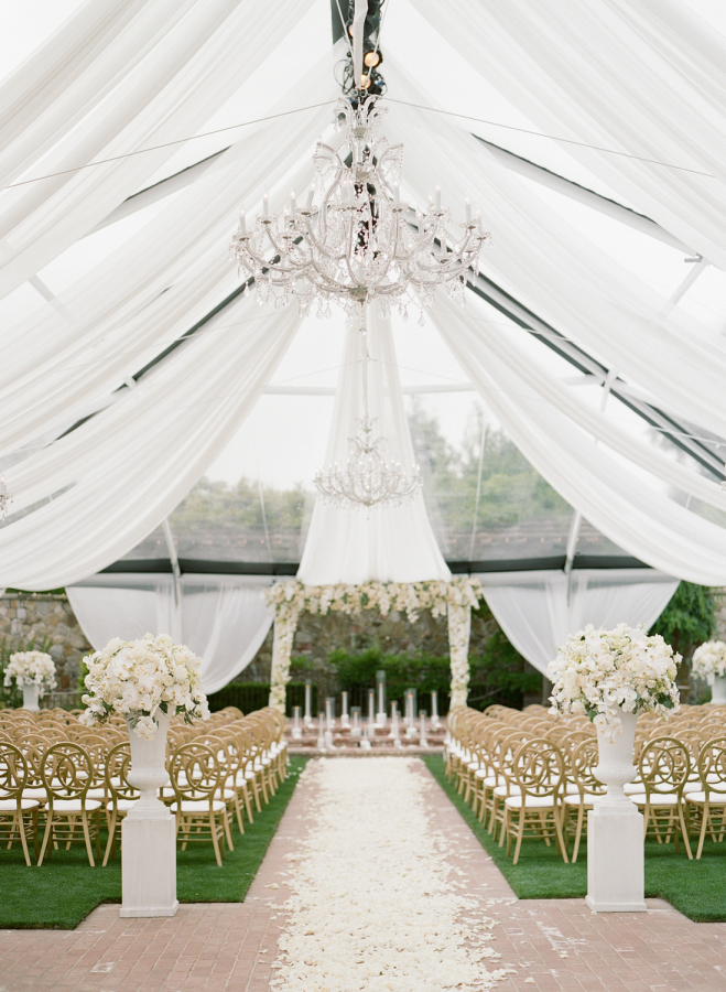 The wedding tent decorated with curtains, lush white florals and petals