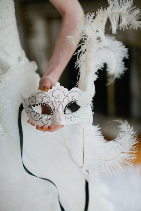 a sparkling white mask with feathers
