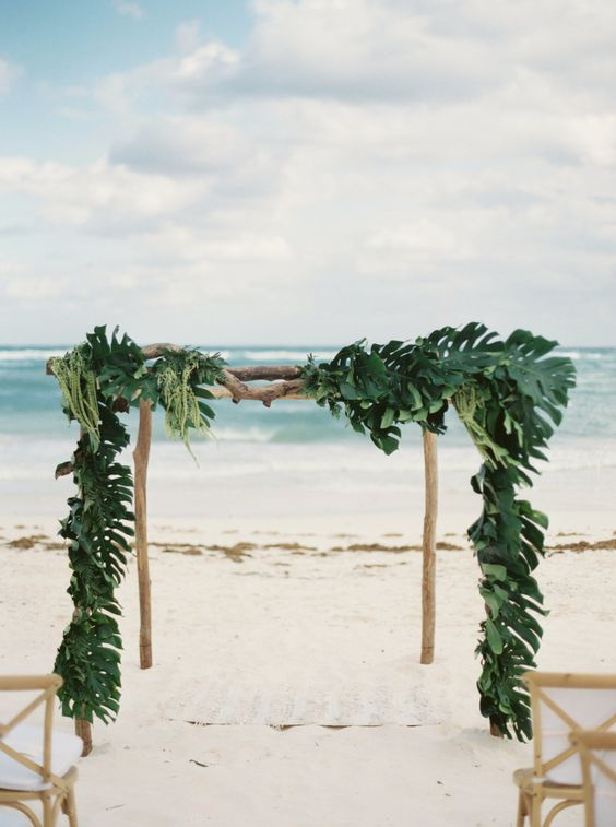 a wooden wedding arch covered completely with palm leaves