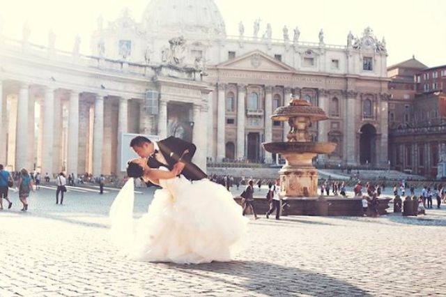 the happy couple kissing in the center of Rome in sunlight