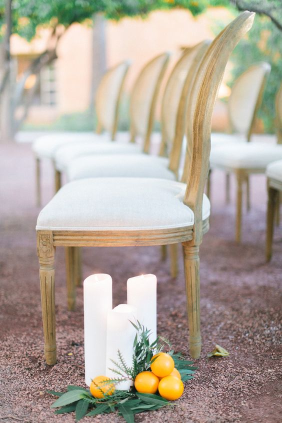 white candles, greenery and citrus for unique aisle decor