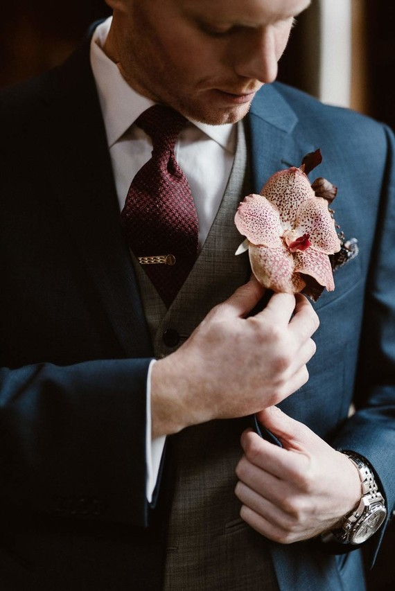 A large tropical flower boutonniere was an unexpected touch to the elegant vintage-inspired groom's look