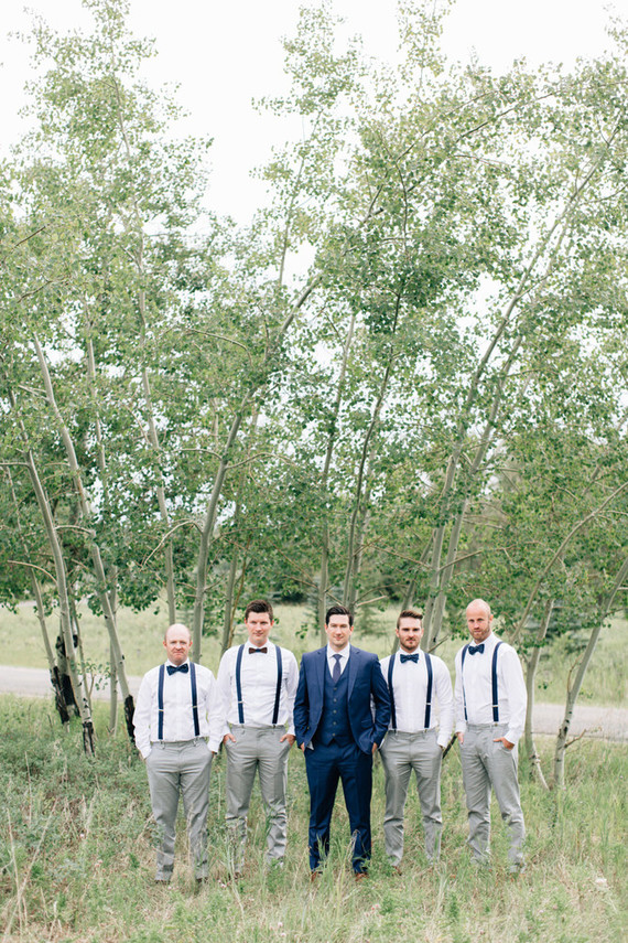 The groomsmen rocked grey pants, white shirts and navy suspenders and bow ties