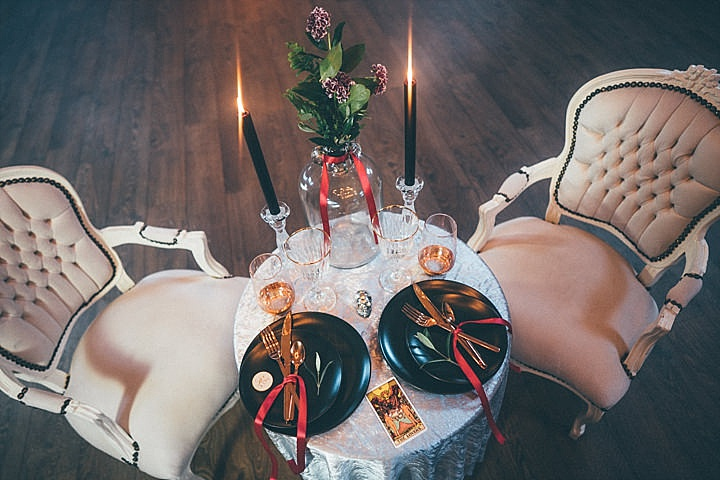 The table was laid with black candles and plates, with dark florals and tarot