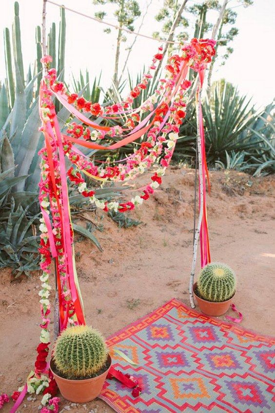 a colorful wedding arch with bold flowers, ribbons and cacti